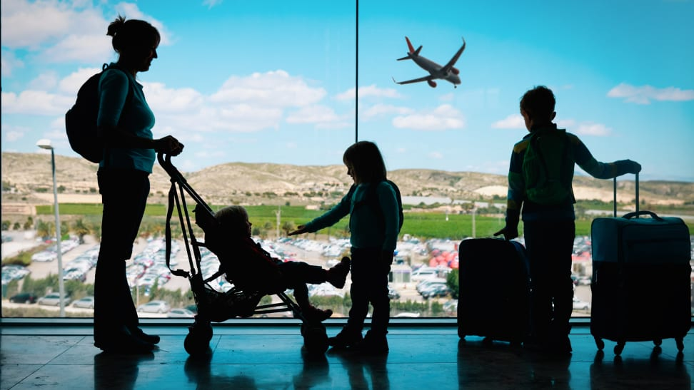 Mother at airport with three kids and luggage