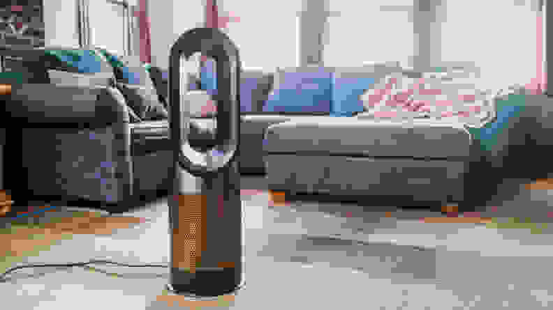 A Dyson air purifier sits at the center of a living room near a blue sectional and matching ottoman.