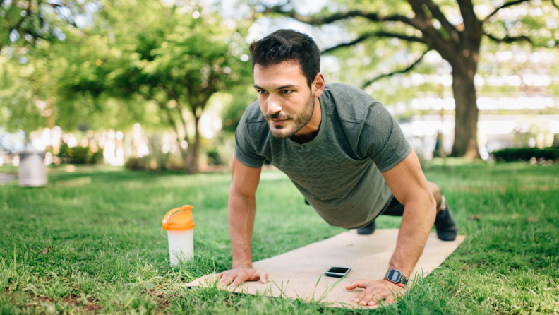 A man on a yoga mat in a park.