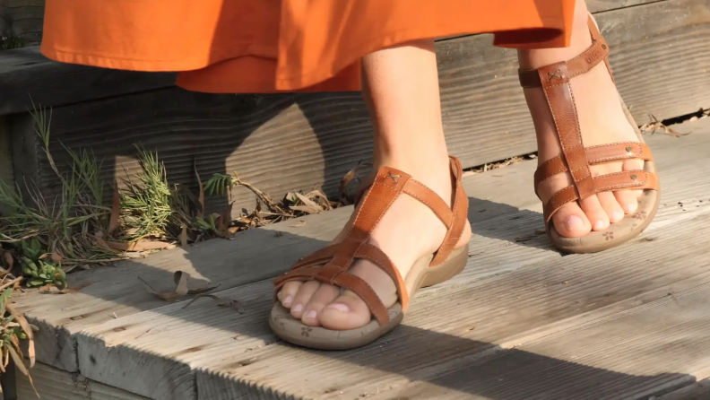 Woman wearing red strappy sandals.