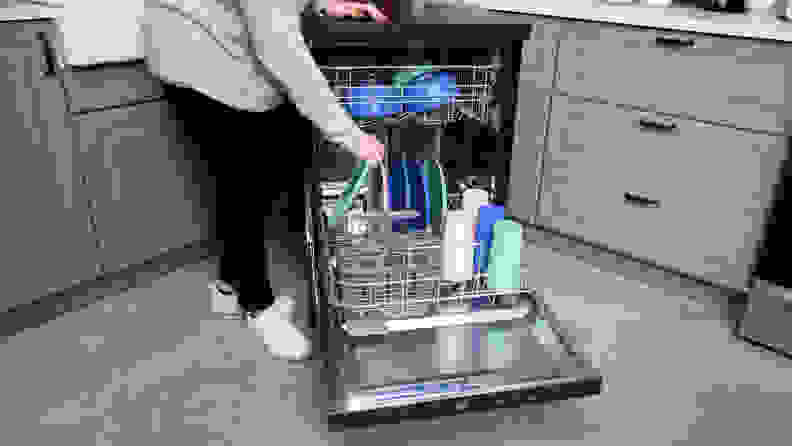 The GE GPT225SSLSS portable dishwasher,open and being filled with colorful pastel dishes.