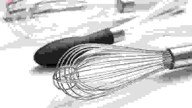 A closeup photo of a balloon whisks with other whisk types in the background.