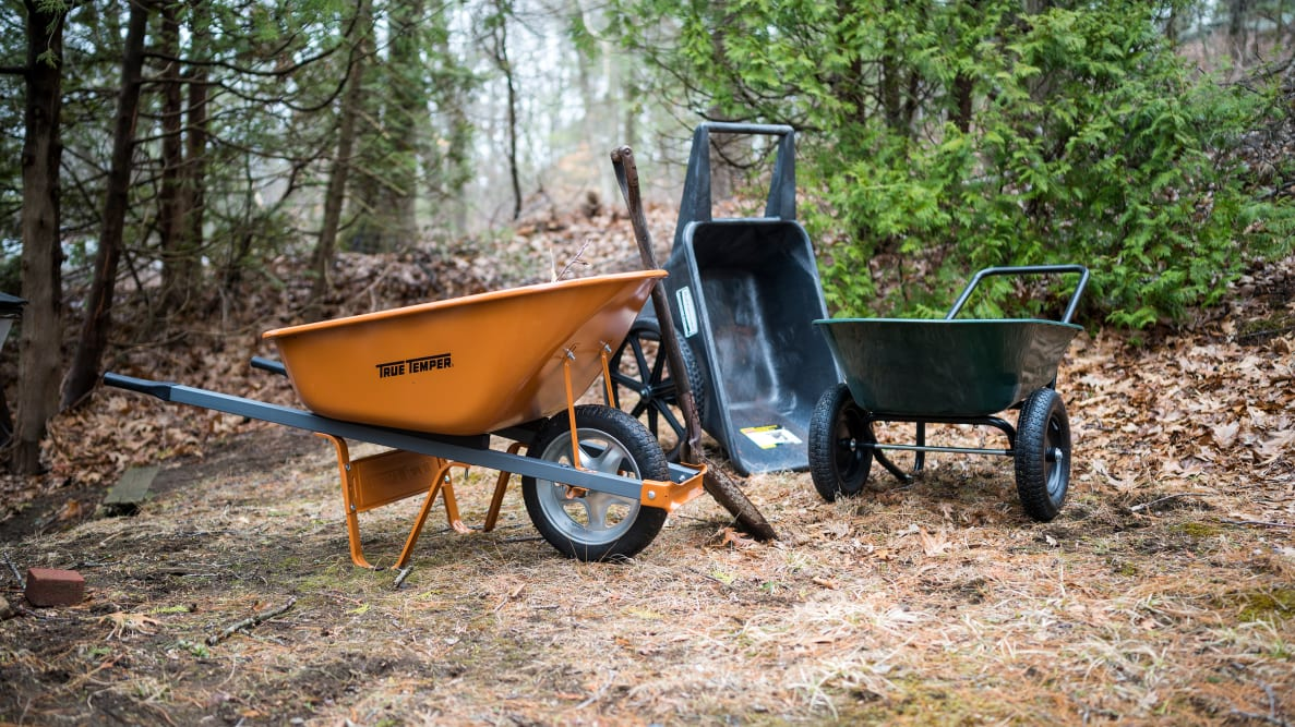 Three wheelbarrows—orange, black, and green—sit in a wooded area.