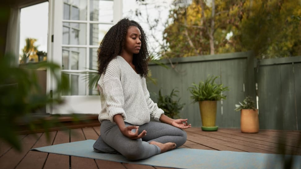 a woman sits on her deck meditating