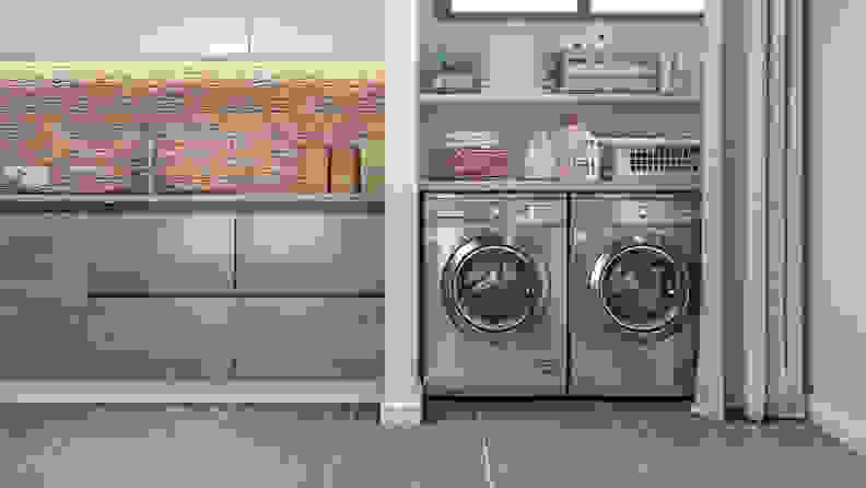 A stainless-steel washing machine and dryer nestled in a laundry room.