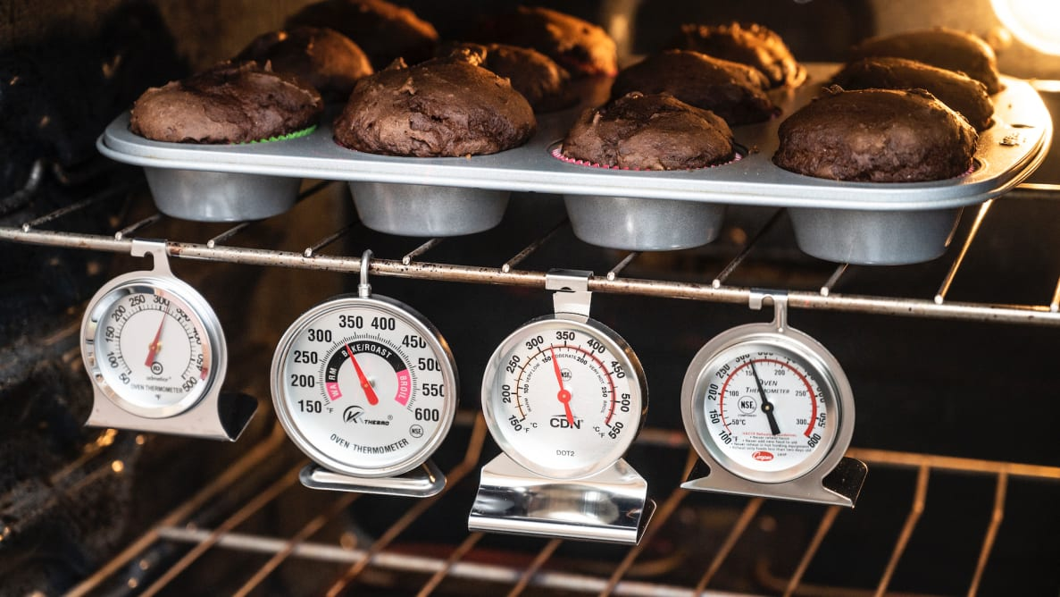 Four of the best oven thermometers Reviewed tested hang inside an oven under a tray of chocolate muffins.
