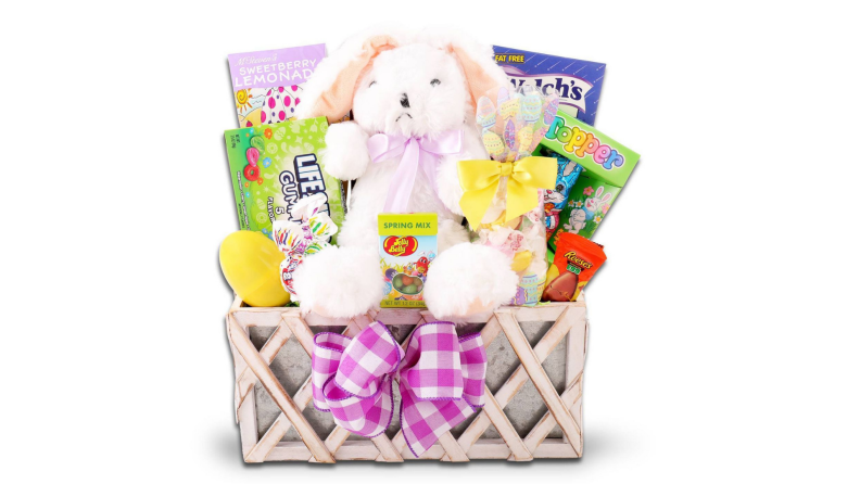 A wooden Easter basket with a stuffed white bunny and candy.
