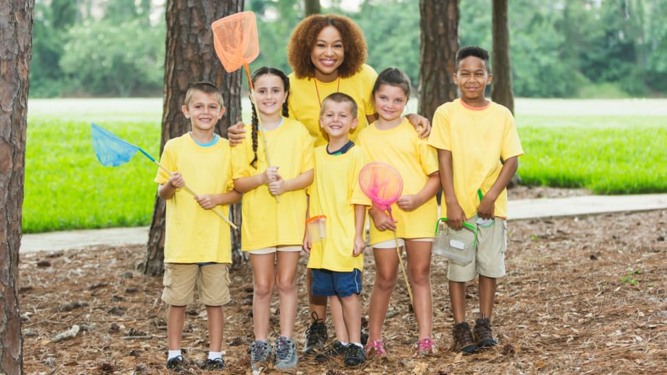 A group of five young children are joined by their camp counselor outside.