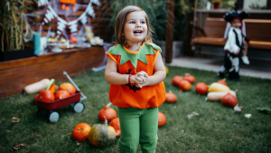 Child smiling outdoors while dressed in jack-o'-lantern Halloween costume.
