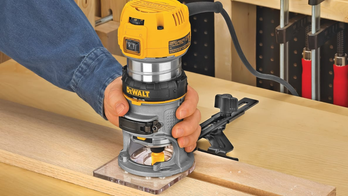 A person saws a plank of wood with the Dewalt DWP611 Compact Router.