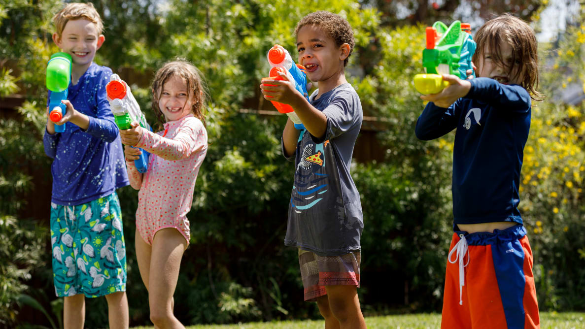 Four kids lined up outside shooting water guns and Nerf Super Soakers