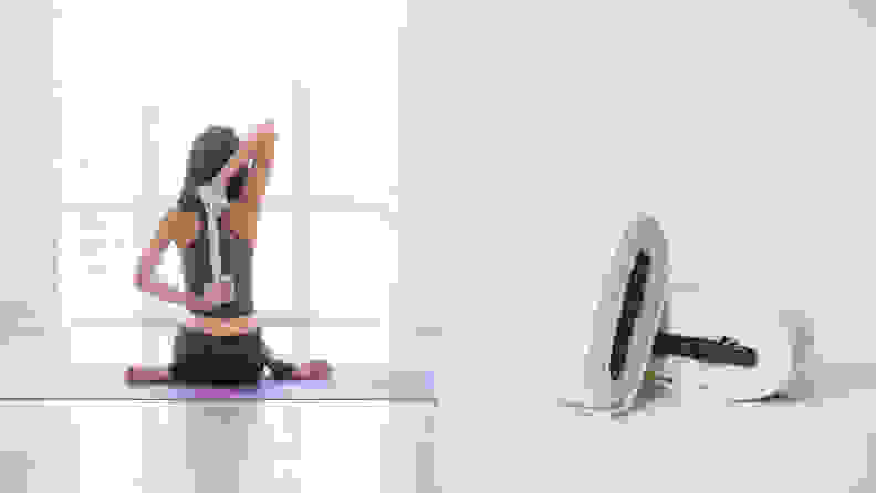 Legs crossed on a mat, bathed in sunlight, a person stretches using a yoga strap.
