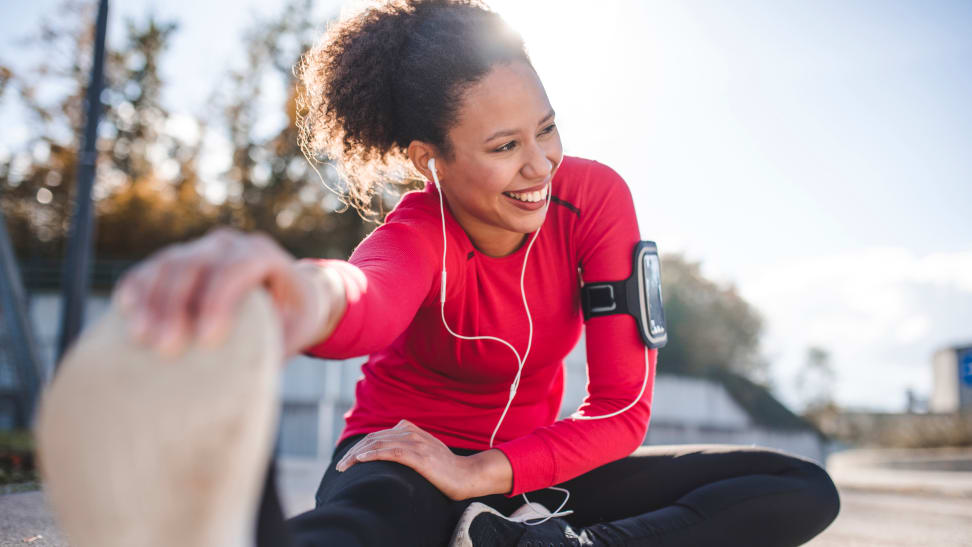 Woman stretching outside wearing headphones and workout clothes.