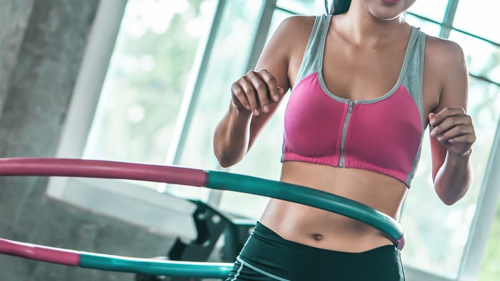 A woman using a hula hoop at the gym.
