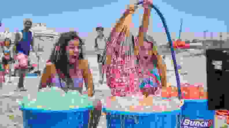 Three girls look on with excitement on buckets filled with full water balloons