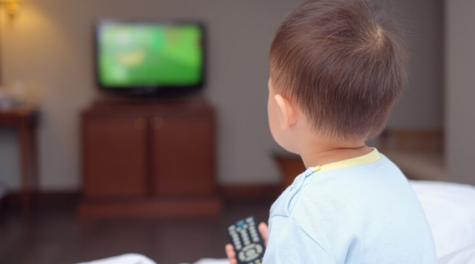 Young child holds remote and looks at a television