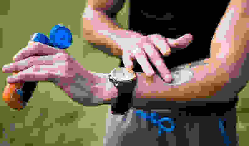 a man applies sunscreen to his arm