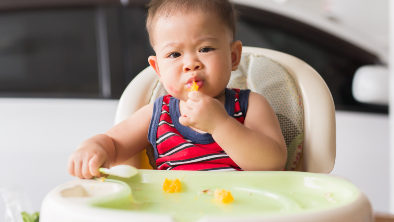 A baby boy in a high chair eating an orange and holding a spoon
