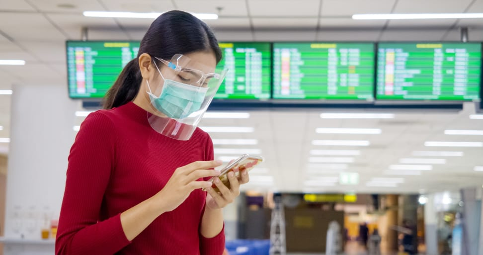 Women wearing red long-sleeved shirt, mask and face shield staring at the smart-phone she's holding while at the airport.
