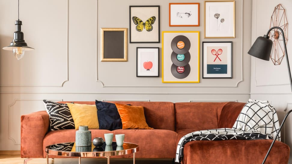 Living room with orange couch with throw pillows, a dining table, a black lamp, and a gallery wall with six art frames