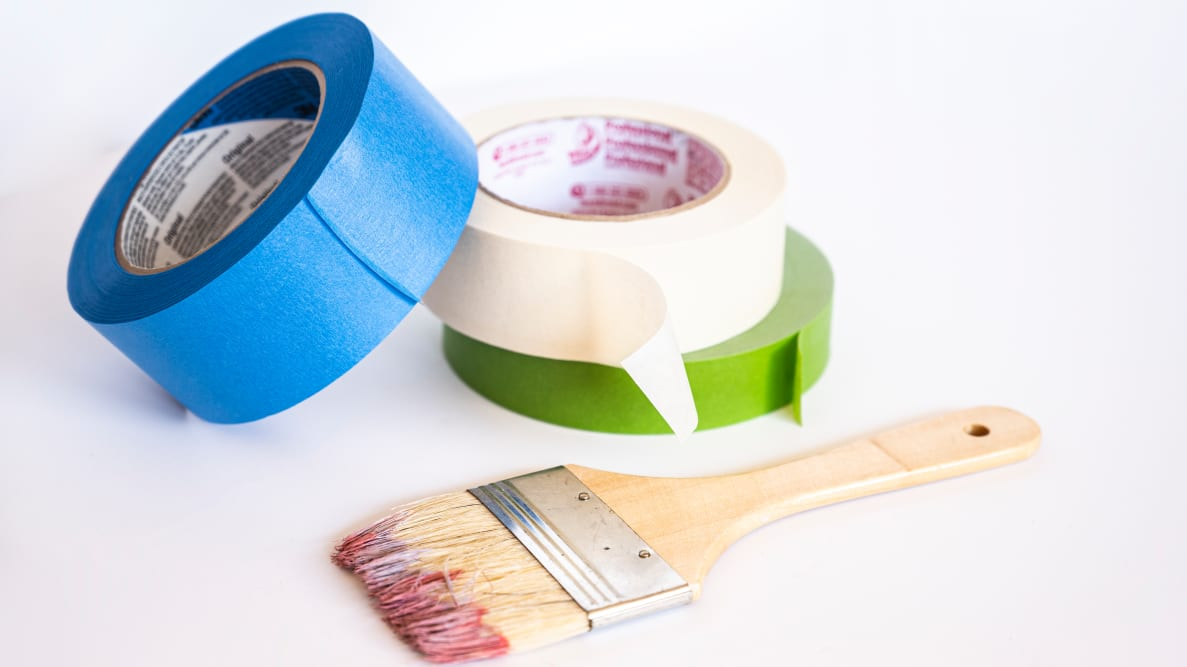 Three painter's tape stacked on top of each other next to a paint brush on a white backdrop