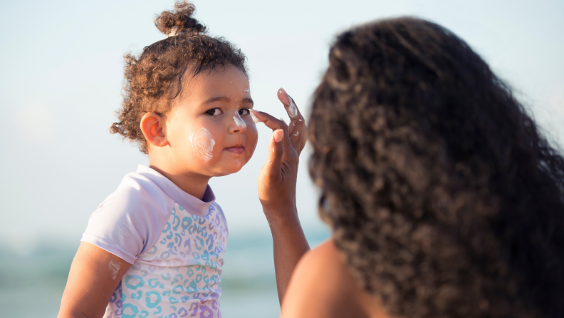 A photo of a woman applying sunscreen to a toddler's face.