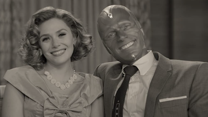 A black and white still from WandaVision featuring Wanda Maximoff and Vision on a sofa in 50s clothes.