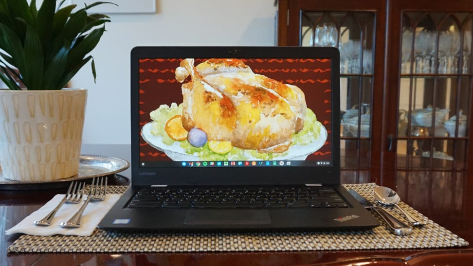 A laptop displaying a picture of a cooked turkey, on a dinner table