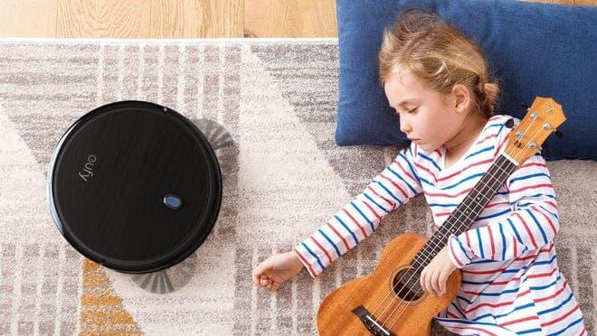 Girl resting on carpet next to sleek black robot vacuum