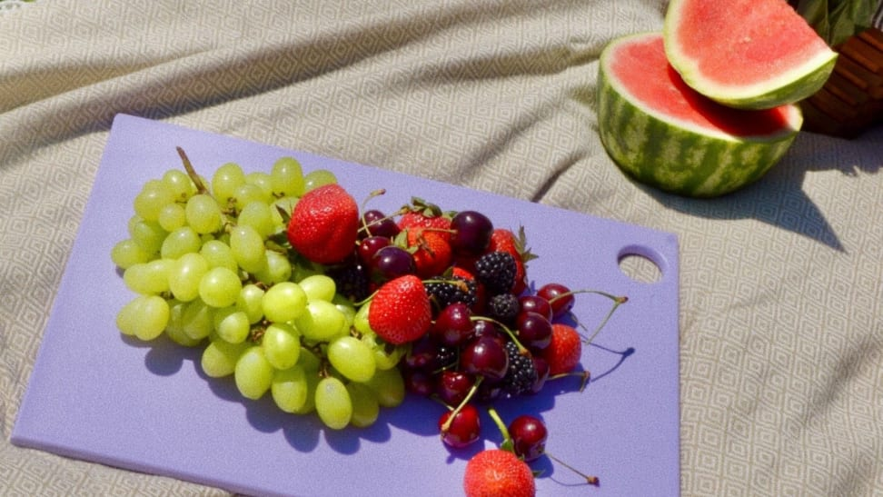 A lilac plastic cutting board with fresh fruit on top, displayed on a picnic blanket.