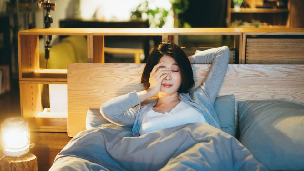 a person sits up in bed stretching before going to sleep