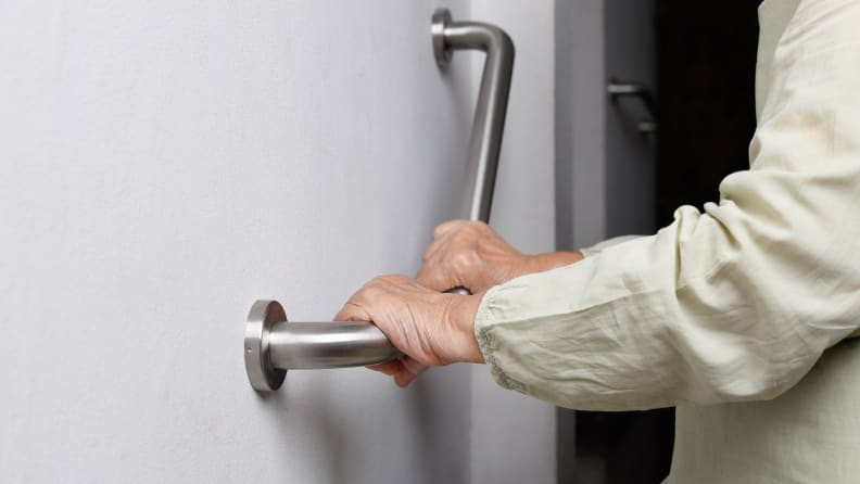 A person holds onto a grab bar inside their home.