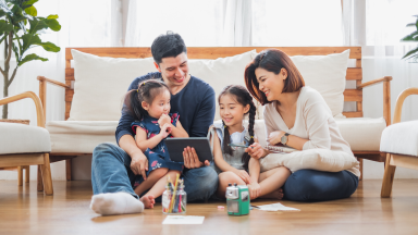 Family huddled around a tablet in the living room