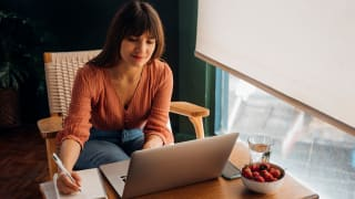 Person writing in notebook while sitting in front of a laptop on a desk near glass of water and bowl of fruit