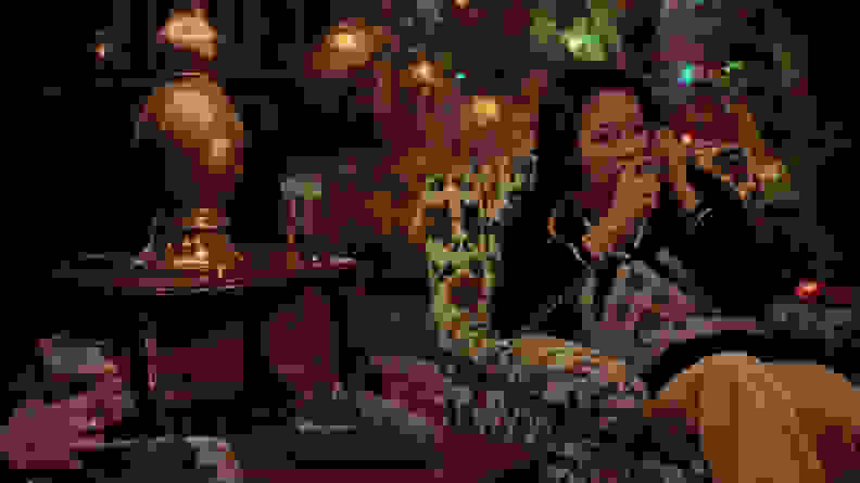Olivia Hussey sitting in a chair, surrounded by Christmas decorations, in a scene from