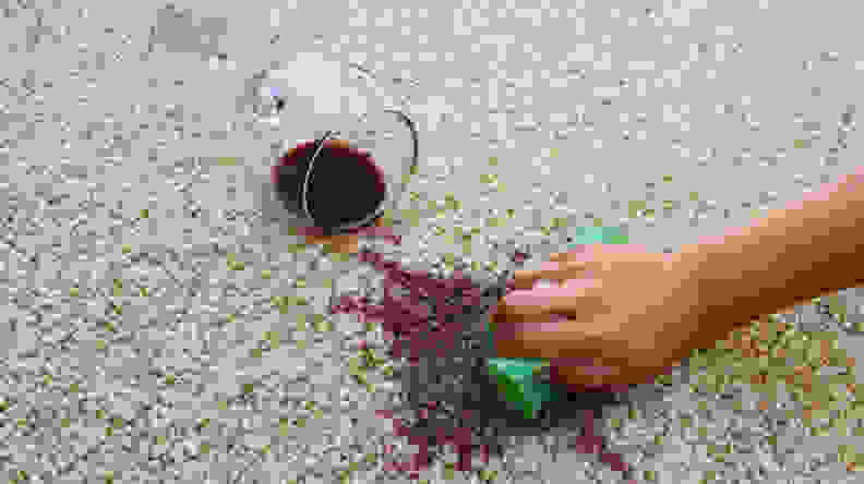 A person tries to sop up red wine that has been spilled on a carpet.