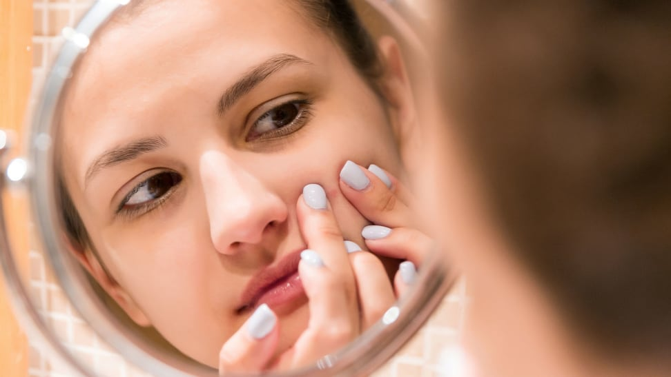 A woman popping a pimple on her face.