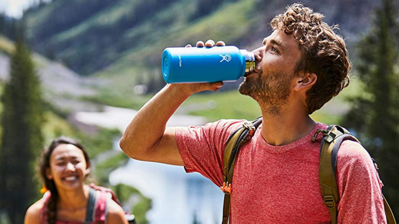A person drinks from a Hydro Flask on a hike.