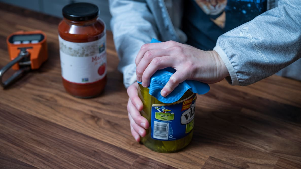 An pair of hands trying to open a jar of pickles