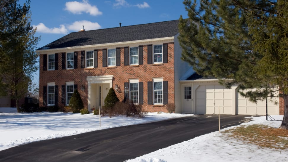 Two-story brick home with an attached garage and asphalt driveway with snow on the ground