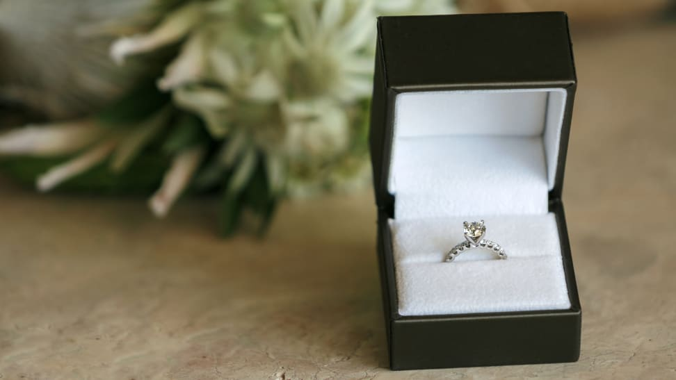 An engagement ring in a jewelry box on a wood table is the perfect kind of inspiration for buying an engagement ring.