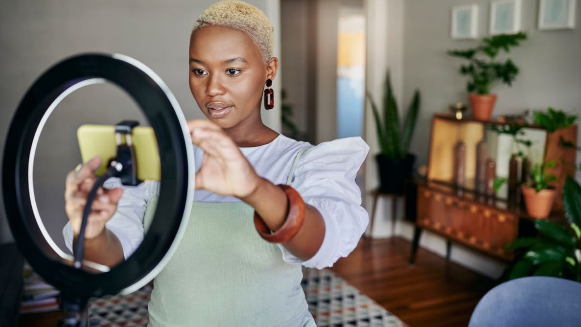 A person recording a video with a ring light and a smartphone.