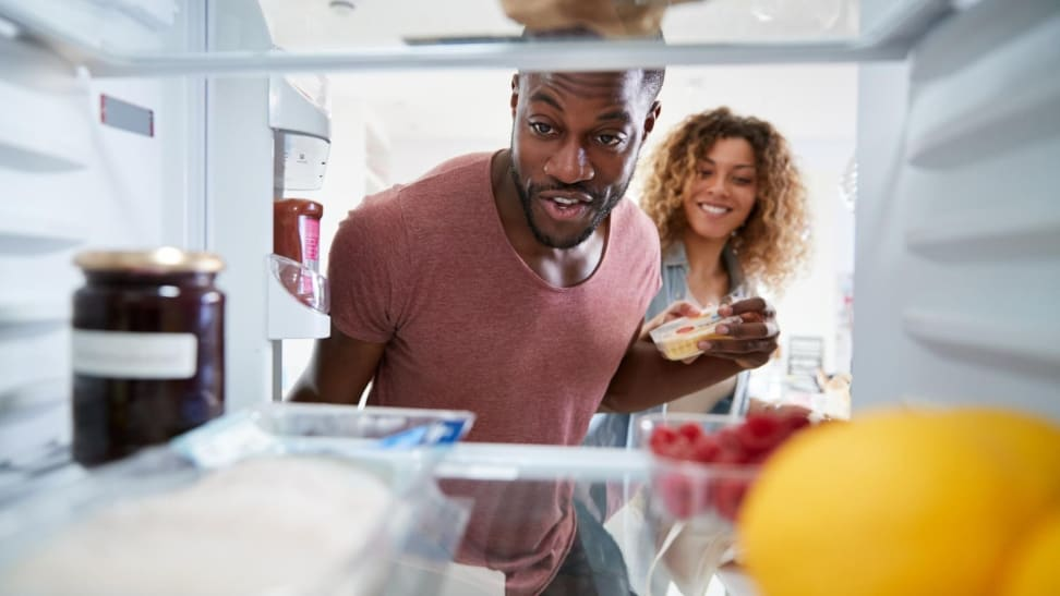 First-time homeowners looking in new refrigerator