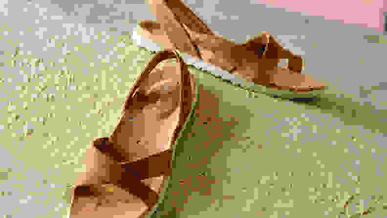 Merrell sandals on a cream background.