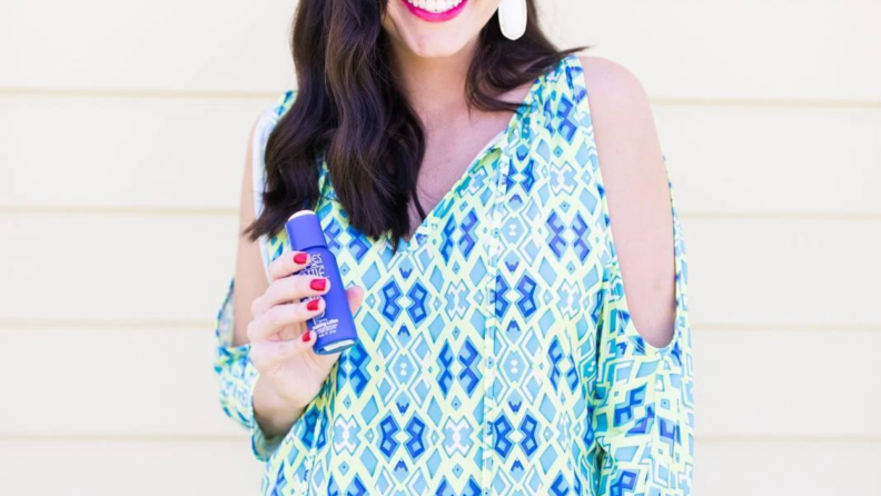 Person smiling while holding bottle of lotion.
