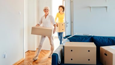 Two people holding boxes move into a new apartment.