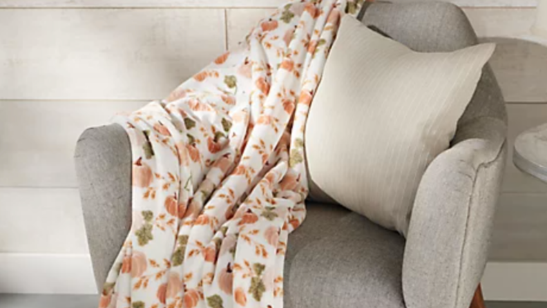 Throw blanket with pumpkins and fall leaves on a chair