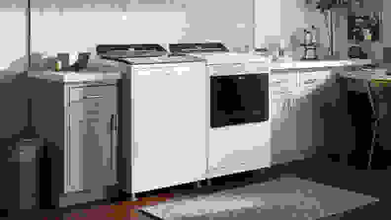 The Whirlpool WTW7120HW top-load washing machine beside a Whirlpool dryer in a laundry room.