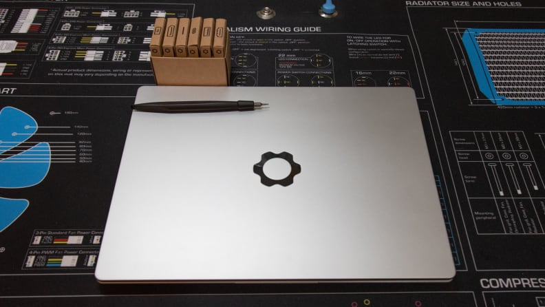 A screwdriver and cardboard box lie on the Framework laptop's lid.
