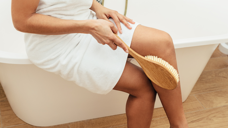A woman sitting on the edge of the tub dry-brushing her leg